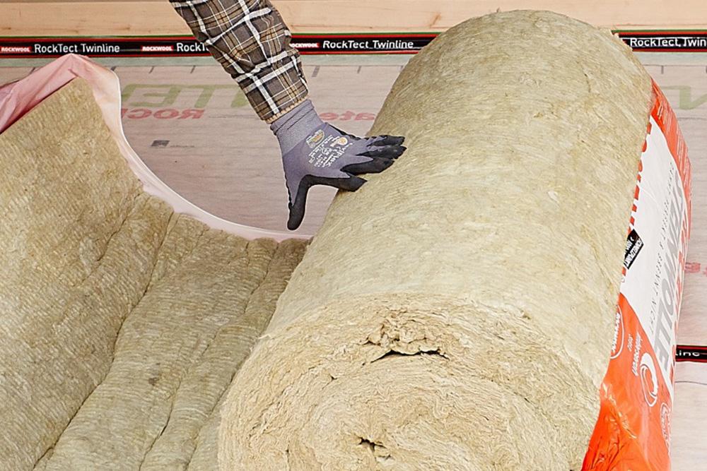 Foto einer Steinwolle Rolle die gerade von einem Verarbeiter geöffnet wird